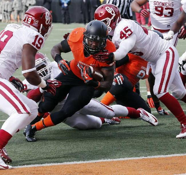 Oklahoma State running back Desmond Roland, center, is stopped short of the goal line by Oklahoma linebacker Caleb Gastelum (45) in the first quarter of an NCAA college football game in Stillwater, Okla., Saturday, Dec. 7, 2013. Oklahoma won 33-24