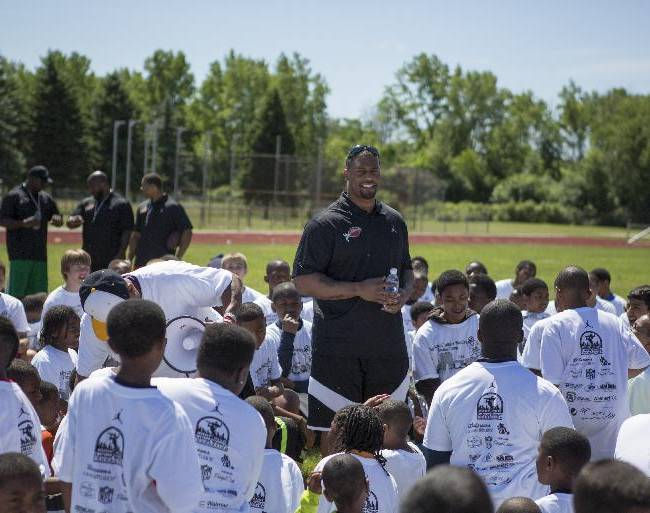 LaMarr Woodley talks to children participating in a football camp that he sponsored at Saginaw High School, Saturday, June 14, 2014. After the camp, Woodley and the other coaches signed autographs for the children