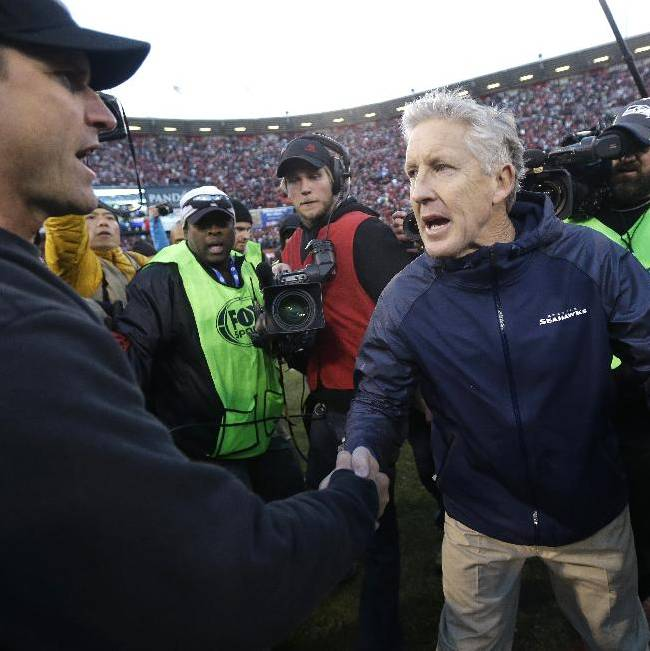 In this Dec. 8, 2013, file photo, San Francisco 49ers head coach Jim Harbaugh, left, shakes hands with Seattle Seahawks head coach Pete Carroll, right, after an NFL football game in San Francisco. The 49ers defeated the Seahawks 19-17. The Seahawks host the 49ers in the NFC championship on Sunday
