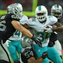 Miami Dolphins' Damien Williams, right, is challenged by Oakland Raiders' Usama Young and Bojay Filimoeatu, centre, during the NFL football game at Wembley Stadium in London, Sunday, Sept. 28, 2014. The Associated Press
