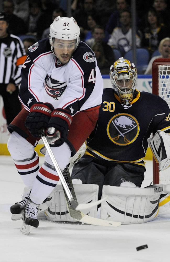 Columbus Blue Jackets center Artem Anisimov (42), of Russia, watches an incoming shot as Buffalo Sabres goaltender Ryan Miller (30) defends during the second period of an NHL hockey game in Buffalo, N.Y., Thursday, Oct. 10, 2013