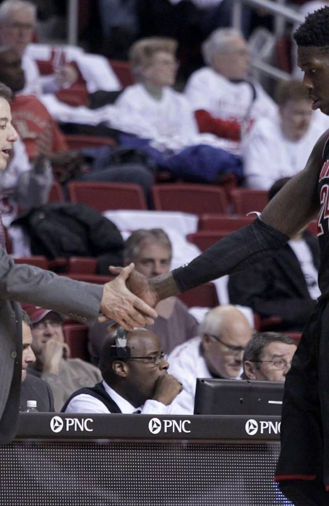 Louisville coach Rick Pitno shakes hands with Monterzl Harrell (24) during the second half against Temple in an NCAA college basketball game, Friday, Feb. 14, 2014, in Philadelphia. Louisville won 58-82