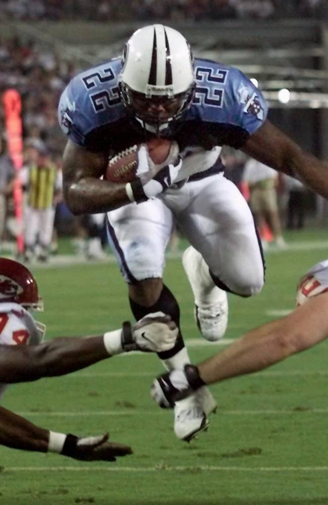 In this Aug. 5, 2000, file photo, Tennessee Titans running back Rodney Thomas (22) jumps between Kansas City Chiefs defenders Jonathan Jackson (94) and Kevin Sluder (62) to score a touchdown in the second quarter of an NFL football game in Nashville, Tenn. A Texas funeral home director says former Houston Oilers and Titans running back Thomas has died at age 41. Groveton Funeral Home owner Terry Cartwright says Thomas died Saturday, June 14, 2014, of an unknown cause and that an autopsy is underway