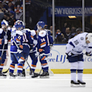 New York Islanders left wing Josh Bailey (12), defenseman Lubomir Visnovsky (11) and defenseman Thomas Hickey (14) celebrate a goal by center John Tavares as Tampa Bay Lightning left wing Brenden Morrow (10) reacts in the third period of an NHL hockey game on Saturday, Dec. 20, 2014, in Uniondale, N.Y. The Islanders won 3-1. (AP Photo/Kathy Kmonicek)