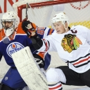 Edmonton Oilers goalie Ilya Bryzgalov (80) and Chicago Blackhawks Jonathan Toews (19) work in front of the net during the second period of an NHL hockey game in Edmonton, Alberta, on Monday, Nov. 25, 2013 The Associated Press