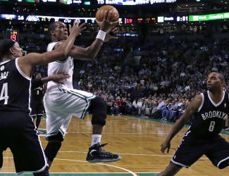 Brooklyn Nets forward Paul Pierce, left, defends Boston Celtics guard Rajon Rondo on a drive to the basket during the first quarter of an NBA basketball game, Friday, March 7, 2014, in Boston. At right is Nets forward Alan Anderson. (AP Photo/Charles Krupa)