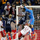 New York Red Bulls goalkeeper Luis Robles (31) makes a save as Sporting Kansas City forward C.J. Sapong (17) attempts to score on a header in the first half during an MLS playoff soccer match at Red Bull Arena in Harrison, N.J., Thursday, Oct. 30, 2014. (AP Photo/Rich Schultz)