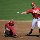 Cincinnati Reds shortstop Zack Cozart, right, throws over Arizona Diamondbacks' Andy Marte, left, to complete a double play on Jordan Parraz in the second inning of a spring exhibition baseball game on Thursday, March 27, 2014, in Goodyear, Ariz The Assoc