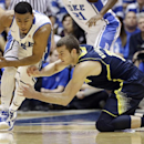 Michigan's Nik Stauskas, right, tries to steal from Duke's Quinn Cook during the second half of an NCAA college basketball game in Durham, N.C., Tuesday, Dec. 3, 2013. Duke won 79-69 The Associated Press