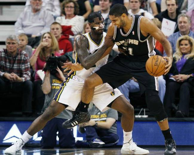 San Antonio Spurs' Tim Duncan, right, looks for an opening as Utah Jazz's Marvin Williams, left, defends in the second half of an NBA basketball game on Saturday, Dec. 14, 2013, in Salt Lake City. San Antonio won the game 100-84