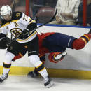 As Boston Bruins' Chris Kelly (23) looks for the puck as Florida Panthers' Erik Gudbranson slams into the wall during the first period of an NHL hockey game in Sunrise, Fla., Sunday, March 9, 2014. (AP Photo/J Pat Carter)