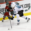 Minnesota Wild left wing Zach Parise (11) and San Jose Sharks defenseman Dan Boyle (22) tangle as they chase the puck during the first period of an NHL hockey game in St. Paul, Minn., Sunday, Dec. 8, 2013 The Associated Press