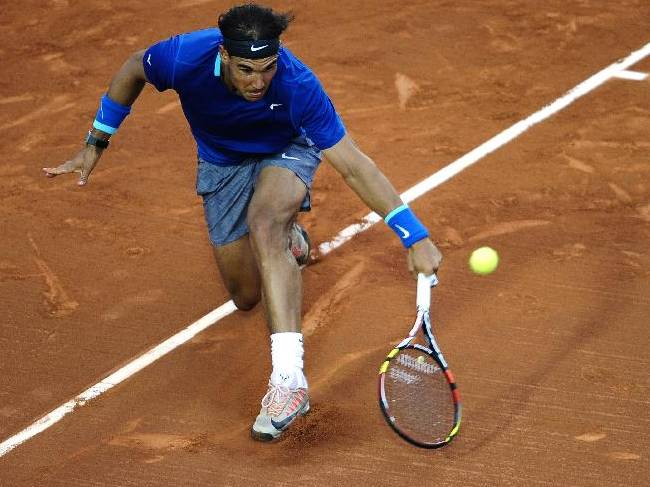 Rafael Nadal of Spain returns the ball to Ivan Dodig from Croatia, during the Barcelona open tennis in Barcelona, Spain, Thursday, April 24, 2014