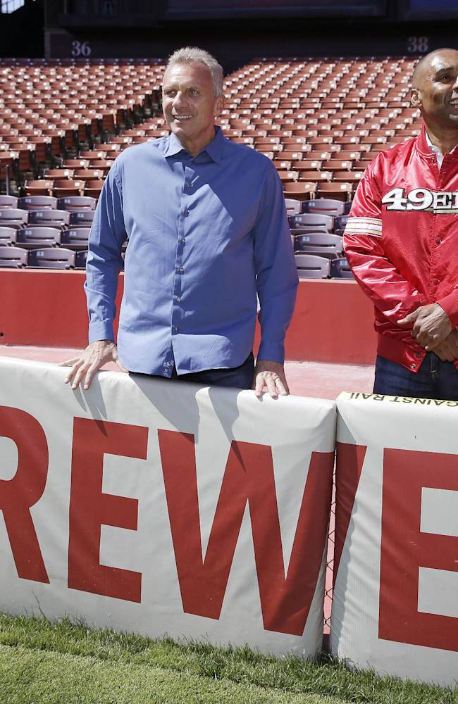 San Francisco 49ers Hall of Fame quarterback Joe Montana, left, and retired running back Roger Craig, right, pose by signage at Candlestick Park after a news conference about their upcoming flag football game Wednesday, June 4, 2014, in San Francisco.