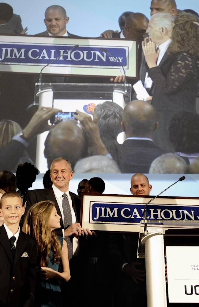 Jim Calhoun, center, holds a street sign of his name as he stands with his family and former players during a program honoring his coaching career at the University of Connecticut, Sunday, Sept. 22, 2013, in Storrs, Conn. Calhoun retired a year ago with 873 wins and 380 losses after 40 seasons as a head coach, 26 of them at Connecticut