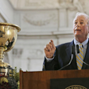 FILE - PGA of America President Ted Bishop speaks next to the Presidents Cup trophy at a news conference at City Hall in San Francisco, in this July 2, 2014 file photo. The PGA of America president referred to Ian Poulter as a little girl on two social media accounts Thursday evening Oct. 23, 2014 for his comments on Nick Faldo and Tom Watson as Ryder Cup captains.(AP Photo/Jeff Chiu, File)