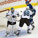 Vancouver Canucks left wing Mike Zalewski (40) tries to get a shot past San Jose Sharks goalie Alex Stalock (32) as San Jose Sharks defenseman Brent Burns (88) looks on during the third period of an NHL preseason hockey game in Vancouver, British Columbia