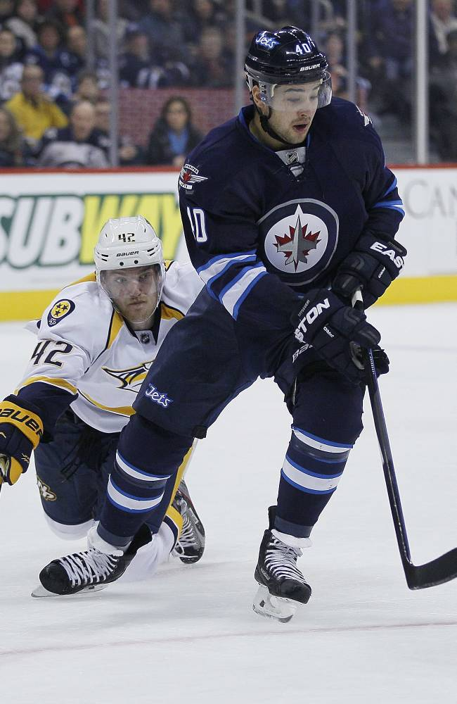 Nashville Predators' Mattias Ekholm (42) comes from behind and tries to steal the puck from Winnipeg Jets' Devin Setoguchi during the second period of an NHL hockey game Friday, Nov. 8, 2013, in Winnipeg, Manitoba