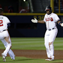 Atlanta Braves' Justin Upton, right, reacts while approached by teammate and brother B.J. Upton after hitting a single to score the winning run in the tenth inning of a baseball game against the Washington Nationals, Friday, April 11, 2014, in Atlanta The