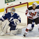 New Jersey Devils' Travis Zajac (19) and Tampa Bay Lightning goalie Ben Bishop (30) watch a rebound bounce in front of the net during the first period of an NHL hockey game Tuesday, Oct. 14, 2014, in Tampa, Fla The Associated Press