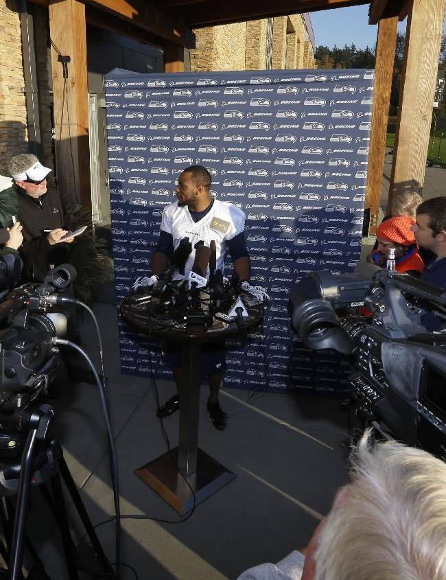 Seattle Seahawks wide receiver Percy Harvin, center, talks to reporters after NFL football practice, Tuesday, Oct. 22, 2013, in Renton, Wash. It was Harvin's first full team practice since he injured his hip during the off-season