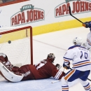 Edmonton Oilers' Mark Arcobello (26) scores a goal against Arizona Coyotes' Mike Smith, left, as Oilers' Justin Schultz (19) looks on during the third period of an NHL hockey game Wednesday, Oct. 15, 2014, in Glendale, Ariz. The Coyotes defeated the Oile