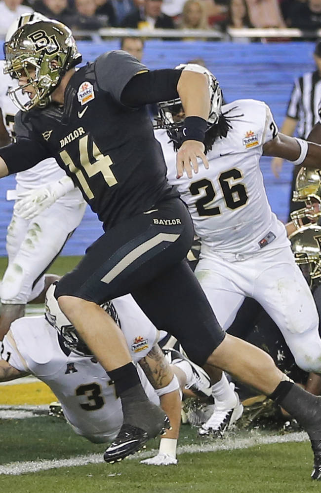 Baylor quarterback Bryce Petty (14) scores a touchdown as Central Florida defensive back Clayton Geathers (26) defends during the second half of the Fiesta Bowl NCAA college football game, Wednesday, Jan. 1, 2014, in Glendale, Ariz