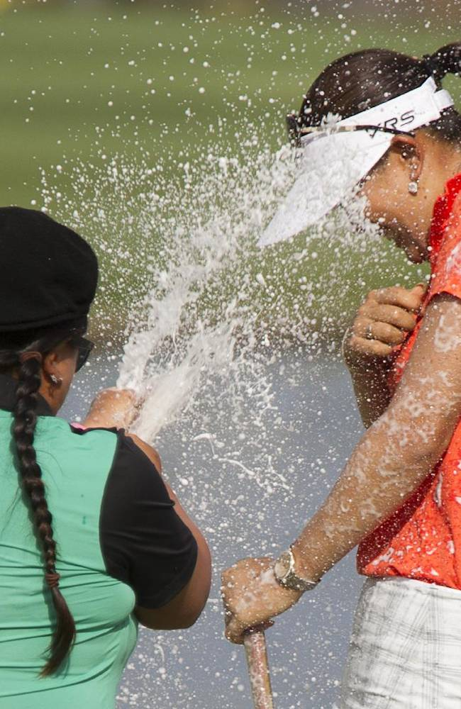 Christina Kim, left, sprays Michelle Wie, right, with champagne, celebrating her win in 2014 the LPGA LOTTE Championship golf tournament at Ko Olina Golf Club, Saturday, April 19, 2014, in Kapolei, Hawaii
