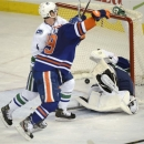 Edmonton Oilers' Sam Gagner celebrates Jordan Eberle's goal, not shown, as Vancouver Canucks Keith Ballard, 4, defends during