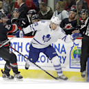 Carolina Hurricanes' Justin Faulk (27) and Toronto Maple Leafs' David Booth (20) chase the puck during the first period of an NHL hockey game in Raleigh, N.C., Thursday, Dec. 18, 2014 The Associated Press