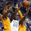 Kentucky's Alex Poythress (22) shoots between Tennessee's Josh Richardson, left, and Yemi Makanjuola during the first half of an NCAA college basketball game at Rupp Arena in Lexington, Ky., Tuesday, Jan. 15, 2013. (AP Photo/James Crisp)