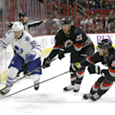 Toronto Maple Leafs' David Booth (20) skates for the puck as Carolina Hurricanes' Riley Nash (20) and Andrej Sekera (4), of Slovakia, defend during the first period of an NHL hockey game in Raleigh, N.C., Thursday, Dec. 18, 2014 The Associated Press