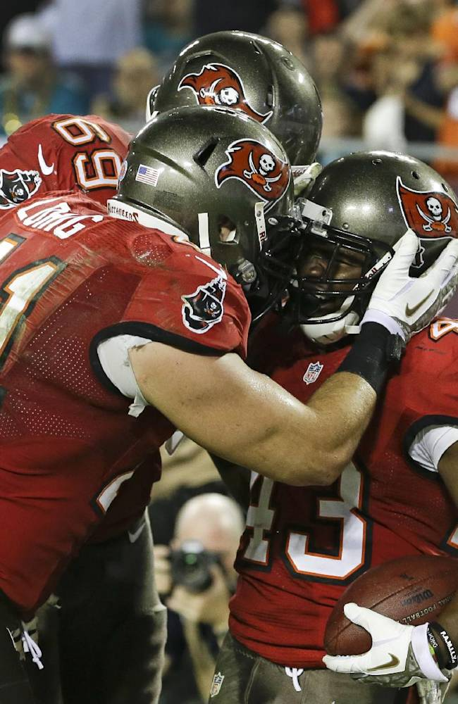 Tampa Bay Buccaneers running back Bobby Rainey, right, celebrates with fullback Erik Lorig (41) and tackle Demar Dotson (69) after scoring a touchdown against the Miami Dolphins on a 1-yard run in the fourth quarter of an NFL football game in Tampa, Fla., Tuesday, Nov. 12, 2013