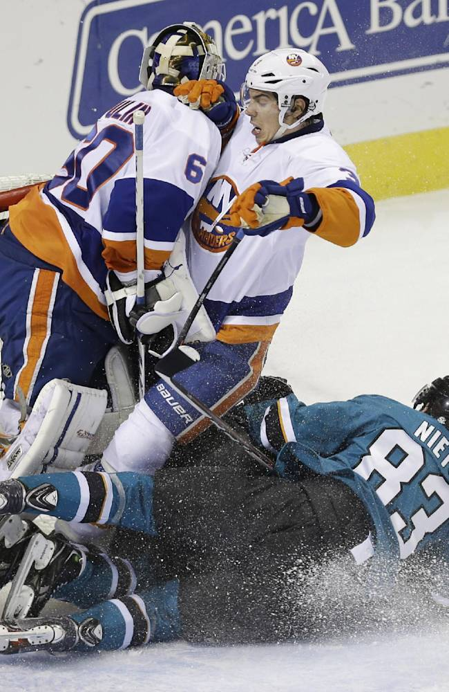 San Jose Sharks' Matt Nieto (83) collides with New York Islanders' Travis Hamonic, center, and goalie Kevin Poulin during the second period of an NHL hockey game on Tuesday, Dec. 10, 2013, in San Jose, Calif
