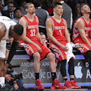 Houston Rockets guard Francisco Garcia (32), guard Jeremy Lin (7), and forward Chandler Parsons (25) sit on the scorers table as they wait for play to resume during the second half of their NBA basketball game against the Brooklyn Nets at the Barclays Cen
