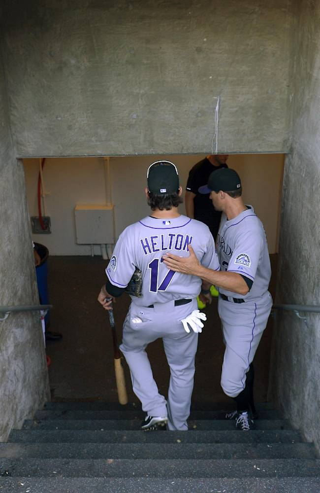 Colorado Rockies' Todd Helton, left, gets a pat on the back from Matt Belisle as he leaves the field after the Rockies defeated the Los Angeles Dodgers 2-1 in a baseball game, Sunday, Sept. 29, 2013, in Los Angeles. Helton was playing in the final game of his career