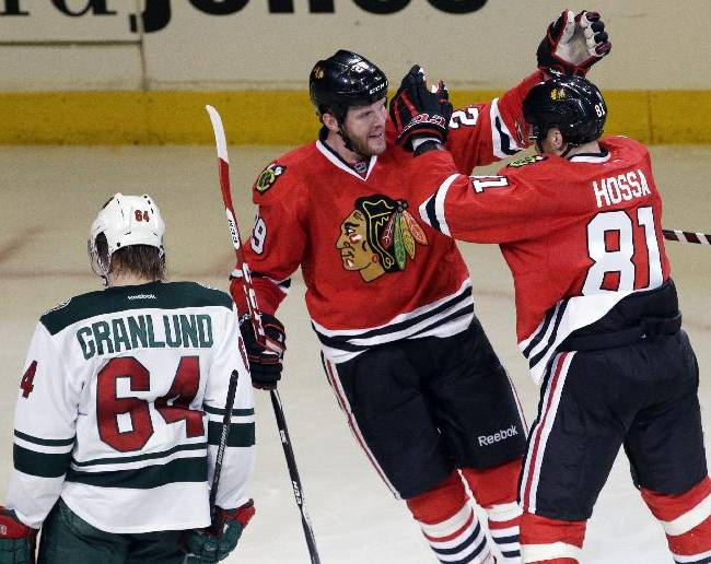 Chicago Blackhawks' Bryan Bickell (29), center, celebrates with Marian Hossa (81), right, after scoring his goal as Minnesota Wild's Mikael Granlund (64) looks down during the third period in Game 2 of an NHL hockey second-round playoff series in Chicago, Sunday, May 4, 2014. The Blackhawks won 4-1