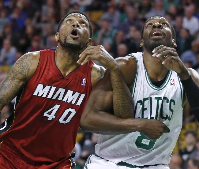 Miami Heat forward Udonis Haslem (40) and Boston Celtics forward Jeff Green (8) lock arms as they fight for position during a free throw in the first quarter of an NBA basketball game in Boston Wednesday, March 19, 2014