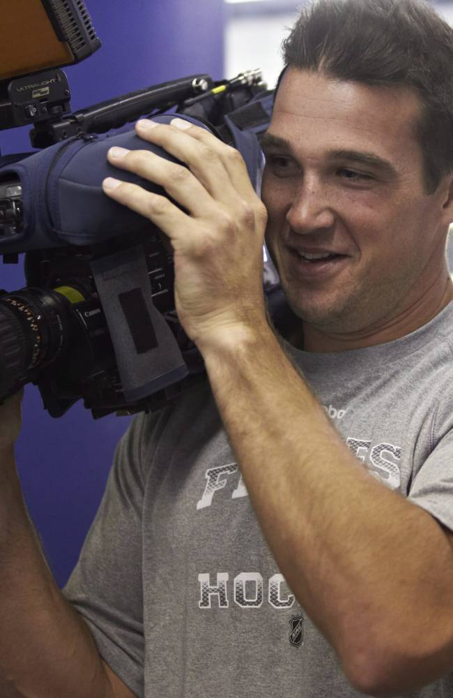 Calgary Flames NHL hockey player Shane O'Brien tries out a TV camera at training camp  in Calgary, Alta., Wednesday, Sept. 11, 2013