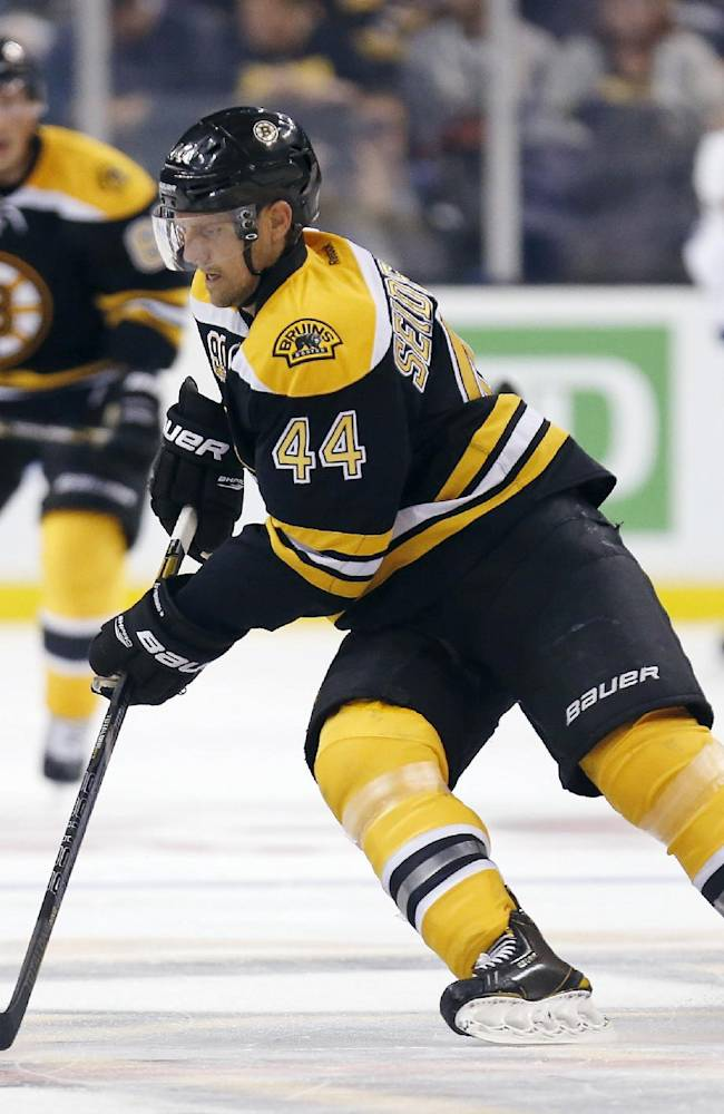 Boston Bruins' Dennis Seidenberg (44), of Germany, handles the puck in the third period of an NHL hockey game against the Tampa Bay Lightning in Boston, Thursday, Oct. 3, 2013