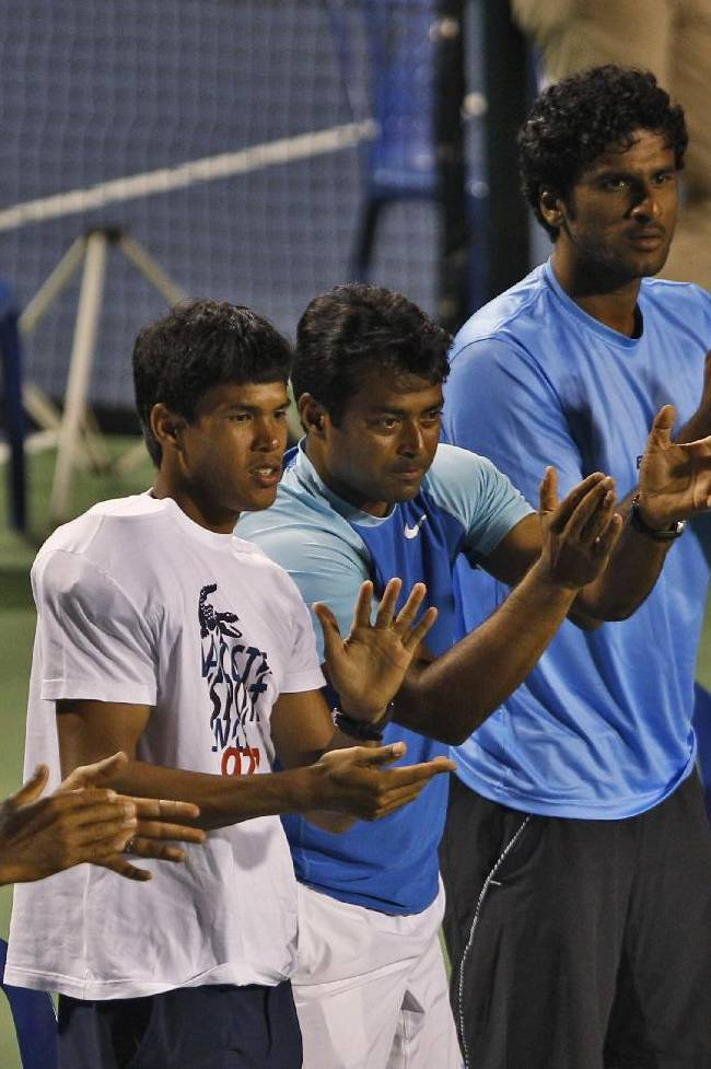 Indian players, from left, Rohan Bopanna, Leander Paes and Somdev Devvarman with others cheer for their teammate Yuki Bhambri at a match against Serbia's Dusan Lajovic during their Davis Cup tennis World Group play-off tie between India and Serbia, in Bangalore, India, Sunday, Sept. 14, 2014