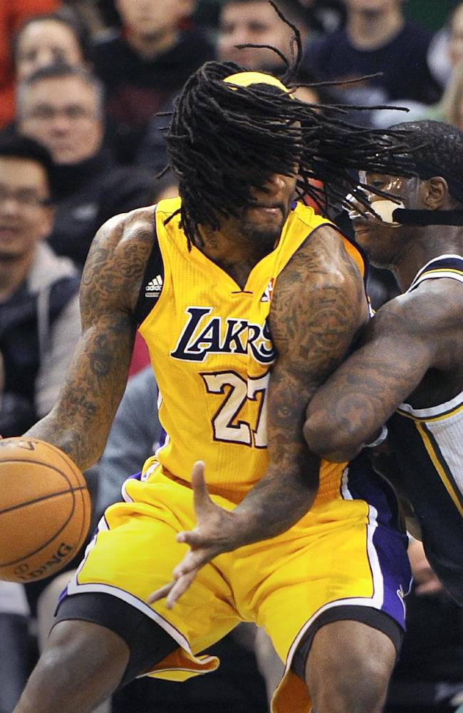 Los Angeles Lakers' Jordan Hill, left, is fouled by Utah Jazz's Marvin Williams during the second half of an NBA basketball game Friday, Dec. 27, 2013, in Salt Lake City. The Jazz won 105-103
