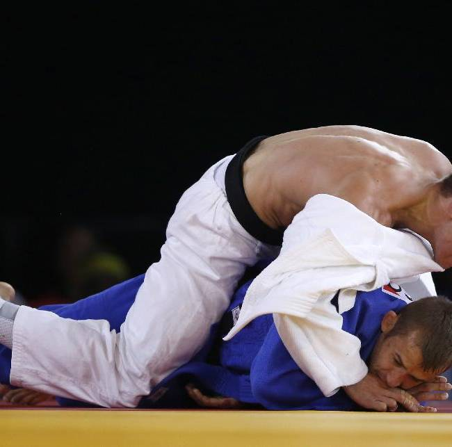 Jan Gosiewski of England, in white top holds down Patrick Dawson of Scotland during their men's 73 kg preliminary round judo contest at the Commonwealth Games Glasgow 2014, in Glasgow, Scotland, Friday, July, 25, 2014