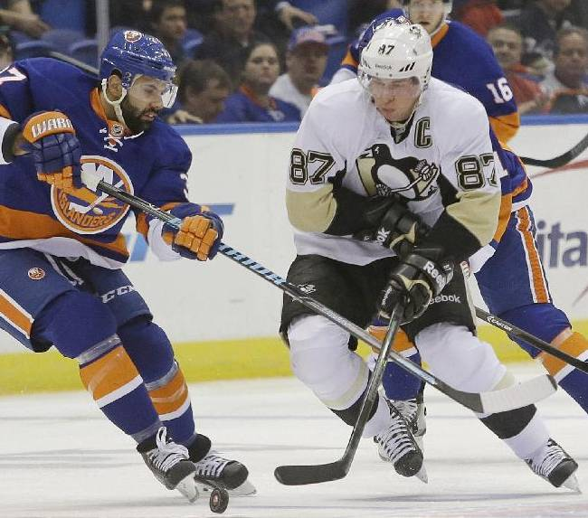 New York Islanders' Brian Strait (37) and Pittsburgh Penguins' Sidney Crosby (87) fight for control of the puck during the first period of an NHL hockey game, Thursday, Jan. 23, 2014, in Uniondale, N.Y