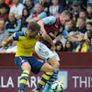 Arsenal's Aaron Ramsey, left, battles for the ball with Villa's Tom Cleverley during the English Premier League soccer match between Aston Villa and Arsenal at Villa Park, Birmingham, England, Saturday, Sept. 20, 2014