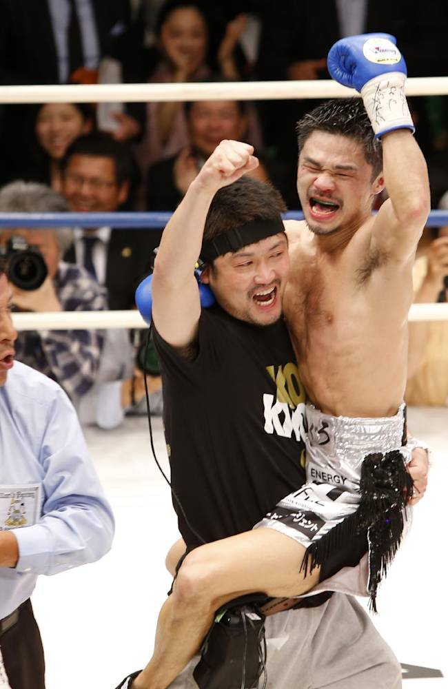 Japan's Kohei Kono celebrates with a member of his team after knocking out Thailand's Denkaosen Kaovichit, left, in the eighth round of their boxing match for the vacant WBA World super flyweight title in Tokyo, Wednesday, March 26, 2014. Kono clinched the title