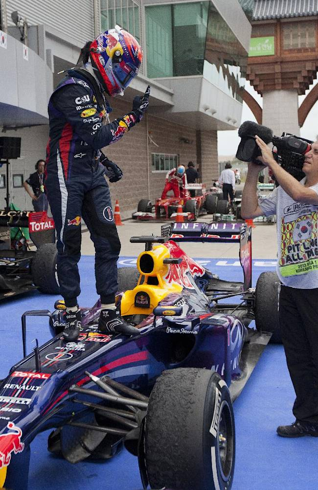 Red Bull driver Sebastian Vettel of Germany gestures to a television cameraman as he celebrates after winning the Korean Formula One Grand Prix at the Korean International Circuit in Yeongam, South Korea, Sunday, Oct. 6, 2013