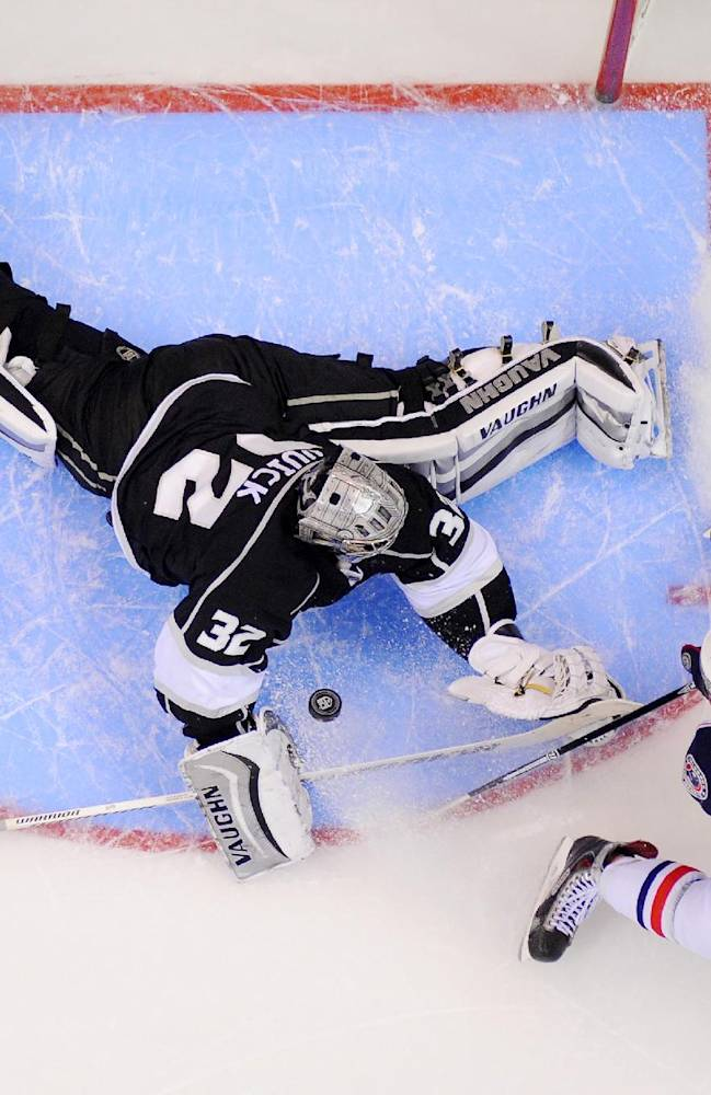 Los Angeles Kings goalie Jonathan Quick, left, stops a shot by Columbus Blue Jackets center Artem Anisimov, of Russia, during the second period of an NHL hockey game, Thursday, Feb. 6, 2014, in Los Angeles