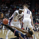 Saint Mary's James Walker III passes the ball from the court covered by Gonzaga's Gary Bell Jr., left, and David Stockton during the first half of a West Coast Conference tournament NCAA college basketball game, Monday, March 10, 2014, in Las Vegas. (AP Photo/Isaac Brekken)