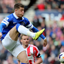 Everton's Ross Barkley, left, has a shot towards goal past Sunderland's Lee Cattermole, right, during their English Premier League soccer match at the Stadium of Light, Sunderland, England, Saturday, April 12, 2014
